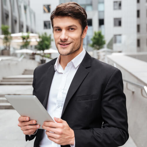 attractive young businessman using tablet near bus P52ZFZH CONSTRUCTORAS EN CANCUN